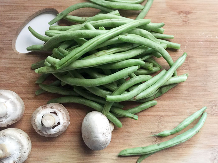 green beans and mushrooms on cutting board