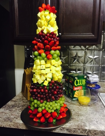 festive fruit centerpiece made with grapes, strawberries, and pineapples