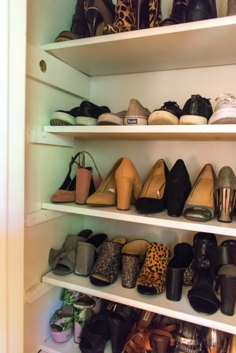 sneakers, pumps, and mules on shelves of shoe closet