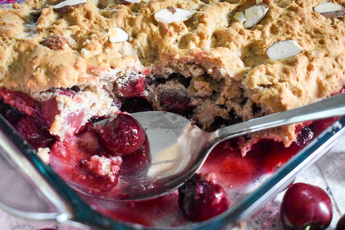 Spiced Cherry Almond Cobbler is bursting with the bright cherry flavor of summer and made quickly and easily with a Bisquik topping plus sliced almonds and sweet spices. Find the recipe on dashofjazz.com
