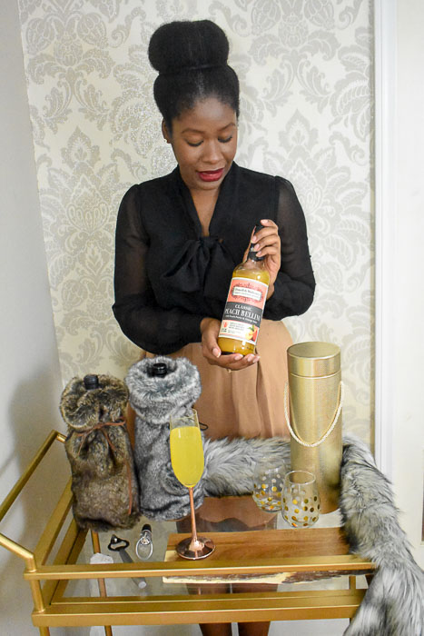 Dash of Jazz holding a mixer, which is one of 6 easy bottle gift ideas for your host