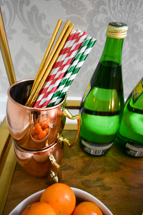 Pretty paper straws in a Moscow mule mug are one of 6 easy bottle gift ideas for your host by Dash of Jazz