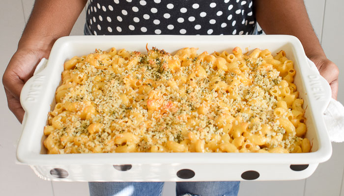 holding pan of brown butter roasted garlic mac & cheese