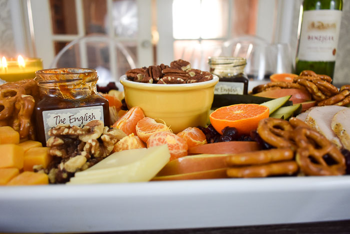 side view of a festive thanksgiving appetizer board with nuts, oranges, pretzels, cheeses, and dipping sauces