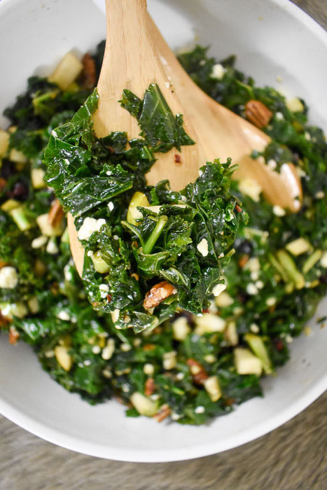 massaged kale salad with crumbled blue cheese, pecans, pears, and cranberries on wooden spoon