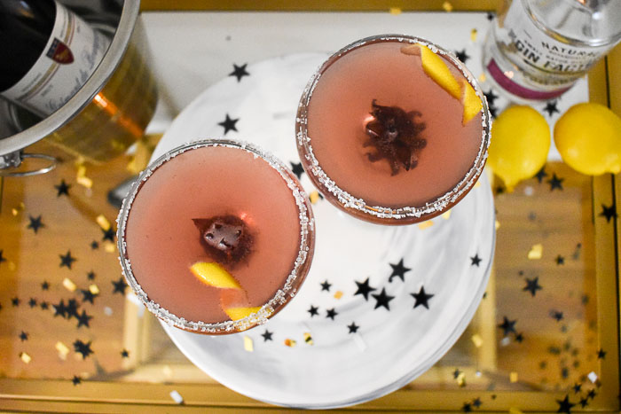Overhead view of two hibiscus French 75 cocktails with lemon garnish and sugar rim