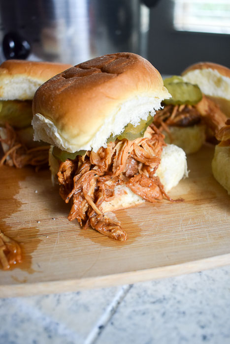 slow cooker pulled bbq chicken on a King's Hawaiian roll with pickles