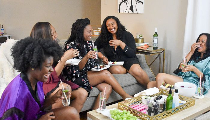 women laughing around coffee table holding glasses of infused water