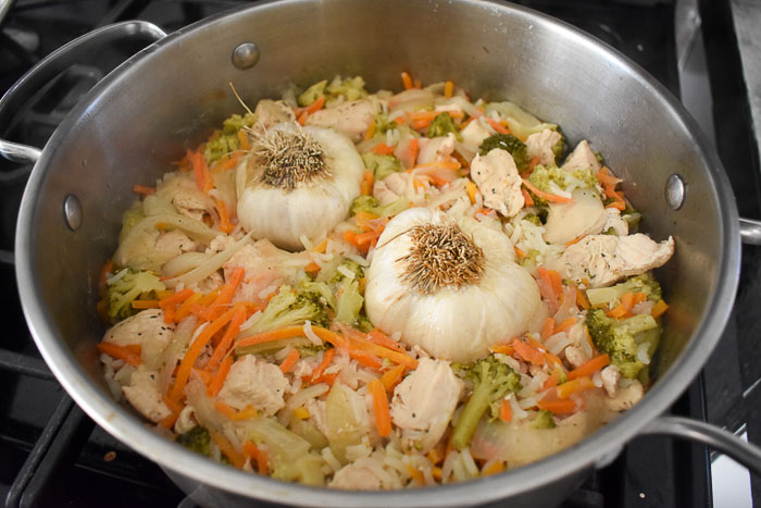 pot of cooked chicken and rice with garlic and vegetables