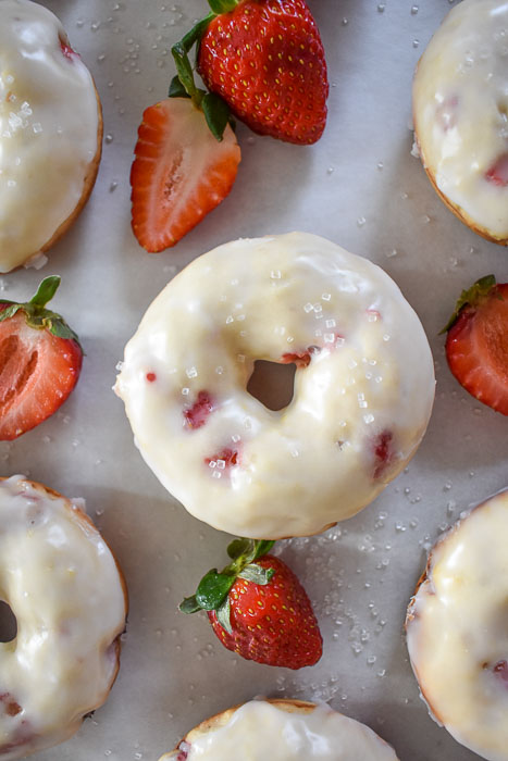 strawberries & champagne donut sprinkled with sugar and surrounded by fresh strawberries