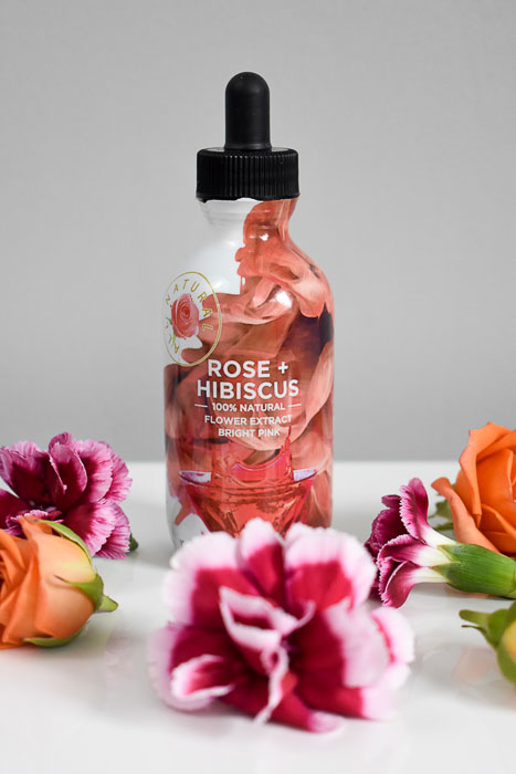 bottle of wild hibiscus flower co rose + hibiscus extract surrounding by fresh flowers