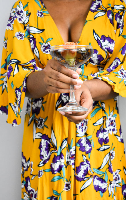 woman holding champagne cocktail glass filled with purple cocktail and an orange flower