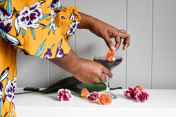 woman placing orange rose garnish on a purple cocktail