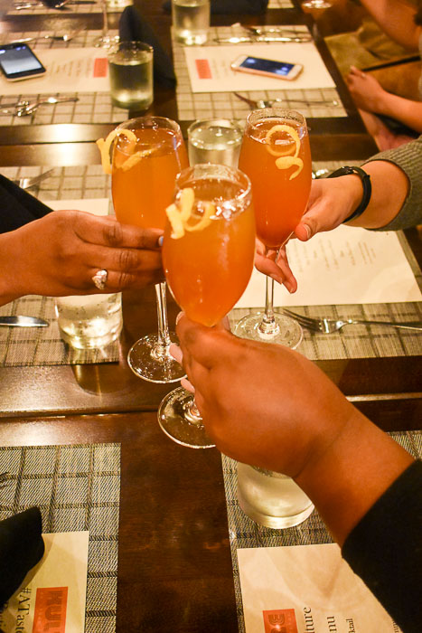 three women toasting cocktails in champagne flutes at Kulture restaurant in Houston, TX