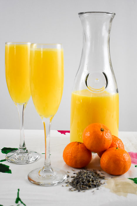 two orange lavender mimosas in champagne flutes, a carafe of orange juice, and four oranges