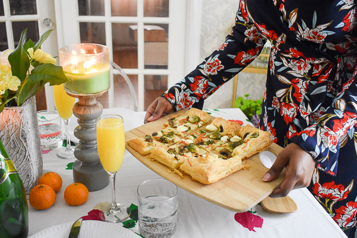 woman placing dish on a spring brunch tablescape