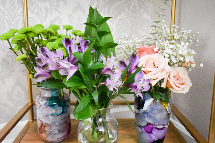 vases filled with greenery, purple alstroemerias, pink garden roses, baby's breath, and green kermit mums