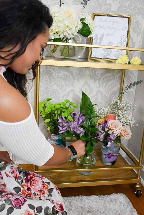 beautiful wavy-haired woman picking fresh flowers from a DIY spring flower bar