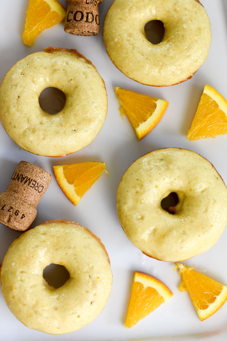 baked mimosa donuts, orange pieces, and champagne corks