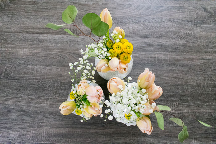 three small floral arrangements on gray tabletop