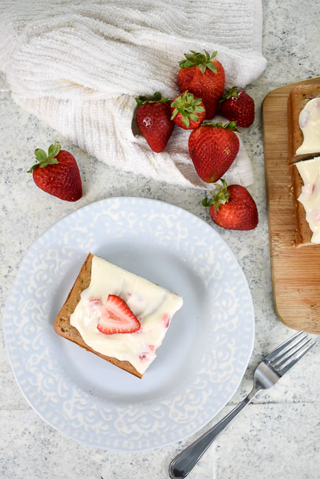 piece of strawberry cream cheese sheet cake on a plate near fresh strawberries