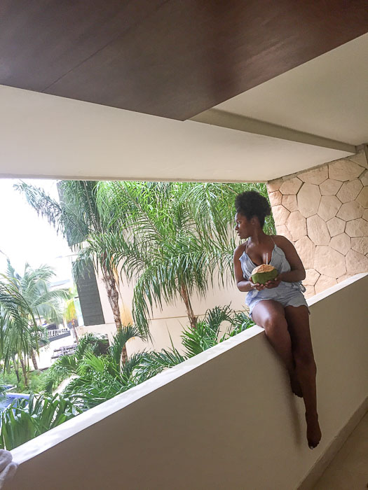 Dash of Jazz looking at Cancun scenery and holding a fresh coconut