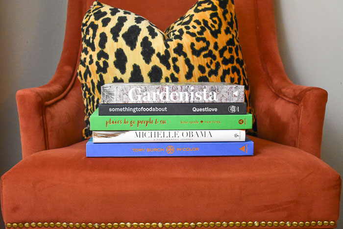 stack of coffee table books and leopard pillow on an orange chair