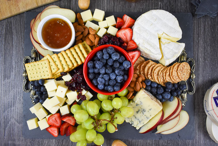 assorted fruits, honey, crackers, nuts, and cheeses on cheese board