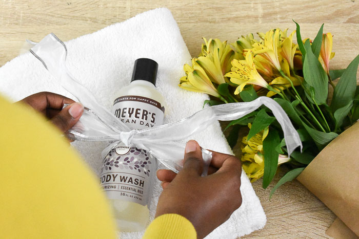 tying ribbon around bottle of Mrs. Meyer's lavender body wash