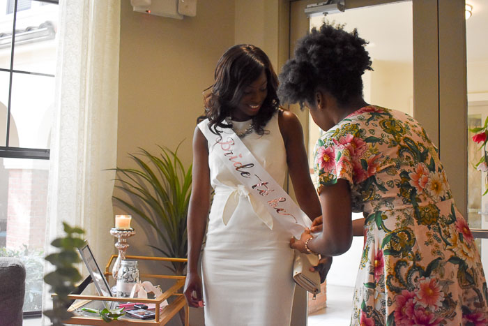 tying bride to be sash on bride at bridal shower