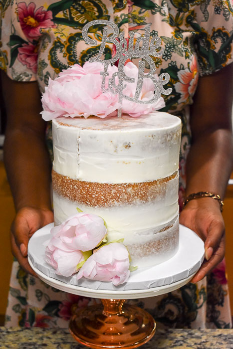 three-layer bridal shower cake with silver topper and pink peonies