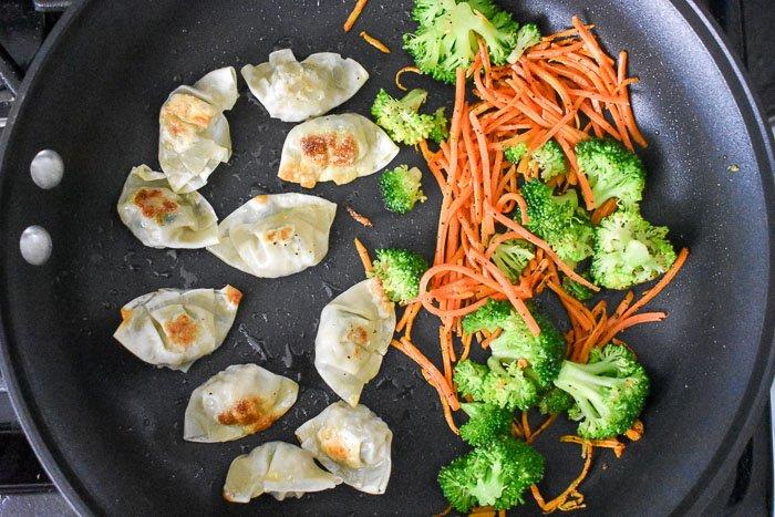 broccoli florets, matchstick carrots, and Bibigo mini wontons pan frying