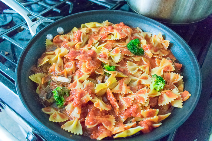 bowtie pasta, vegetables, and crushed tomatoes in skillet