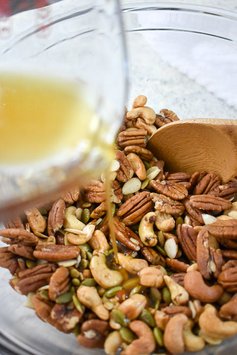 pouring maple syrup mixture into bowl of nuts