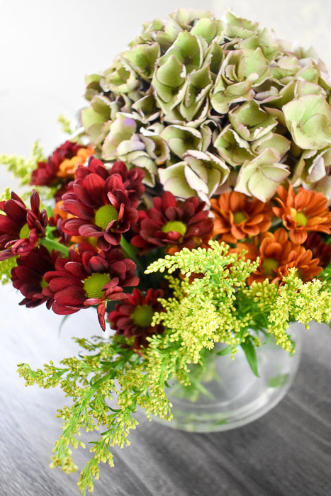 maroon and orange pom pons, goldenrod, and antique hydrangea in glass vase