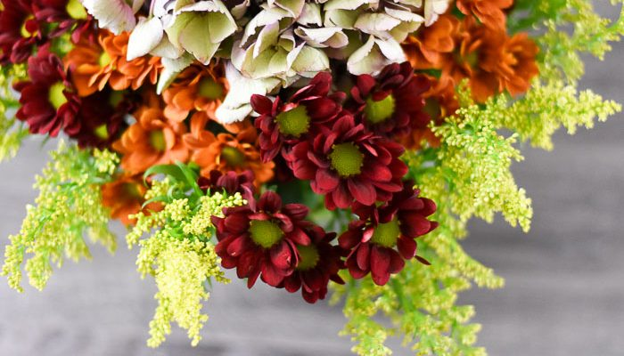 floral arrangement of pom pons, goldenrod, and antique hydrangea