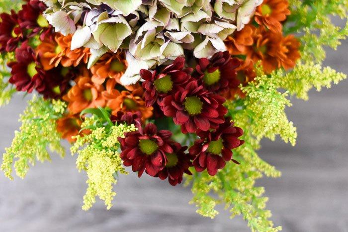 floral arrangement of pom pons, goldenrod, and antique hydrangea