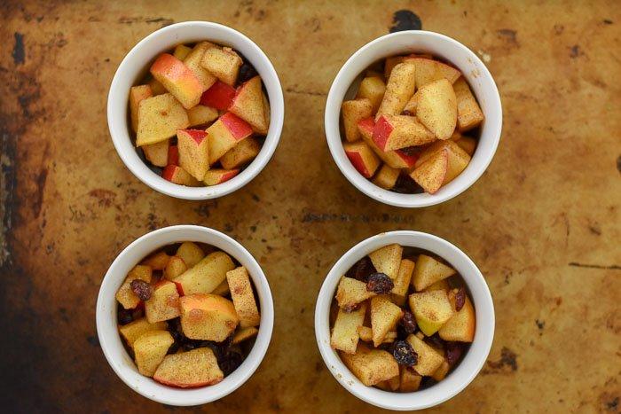 four ramekins filled with apple cranberry crisp filling