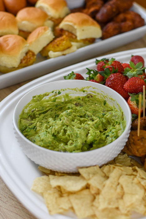 freshly made guacamole in white bowl on tray of appetizers