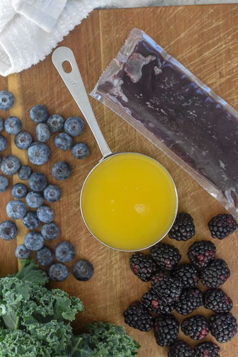 blueberries, blackberries, kale, frozen acai puree pack, and cup of orange juice on cutting board