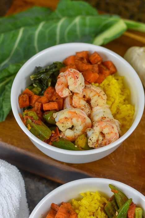 white bowl filled with sauteed shrimp, okra and tomato, yellow rice, caramelized sweet potato, and collard greens