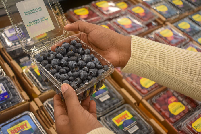 picking up blueberries in clamshell in produce section