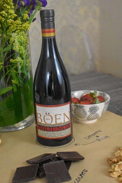 bottle of pinot noir next to dark chocolate and strawberries