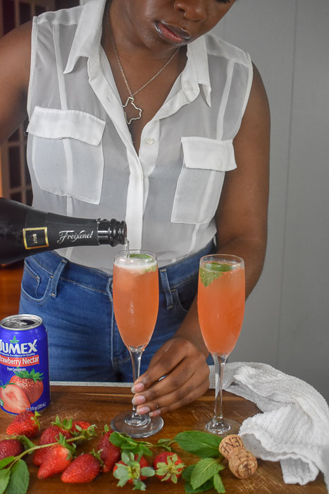 Dash of Jazz pouring champagne into strawberry mint mimosa
