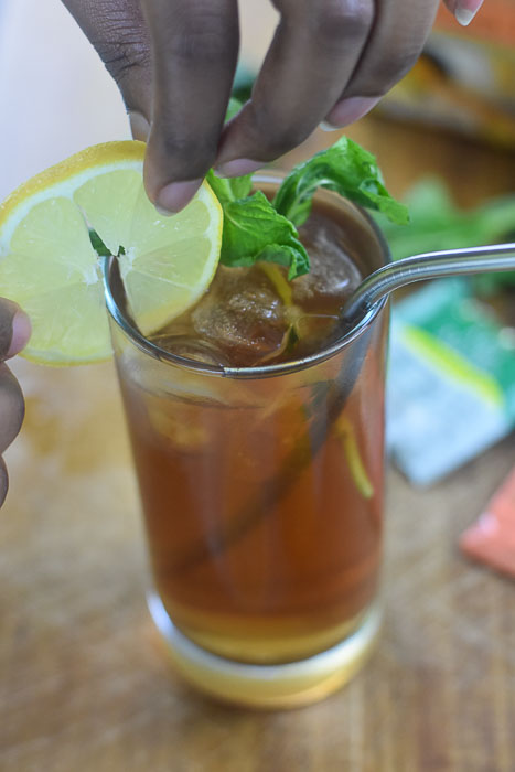 adding lemon slice garnish to glass of iced tea