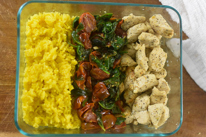 chicken, tomatoes, spinach, and yellow rice packed in Pyrex container