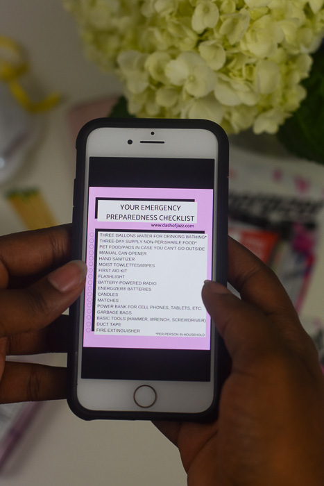 holding iPhone with emergency checklist on screen