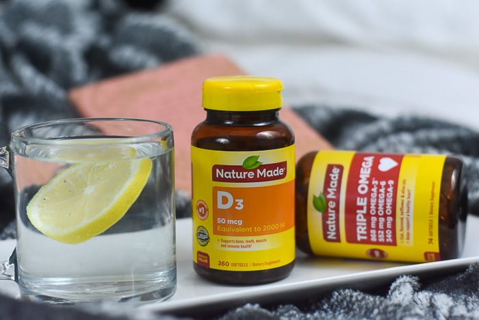 nature made vitamins next to glass of water with lemon