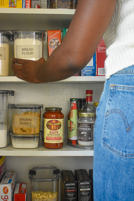 reaching for container of bread flour on pantry shelf