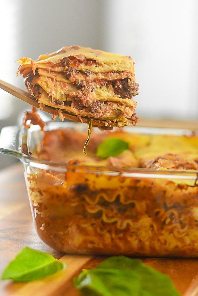 lifting slice of deep dish lasagna out of pan.